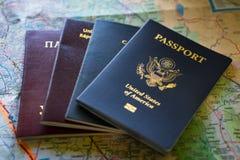 Pasaportes de diversos países en un mapa Fotos de archivo libres de regalías