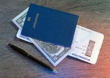 Pasaportes, documento de embarque, dólares, pluma que miente en la tabla de madera Imágenes de archivo libres de regalías