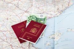 Pasaportes españoles con moneda de la unión europea en un backgrou del mapa Imagen de archivo libre de regalías