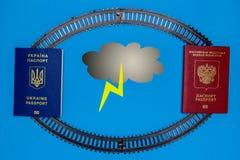 Pasaportes ucranianos y rusos, nubes de papel Concepto de cancelación de la amenaza de la comunicación ferroviaria foto de archivo