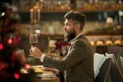 Pasar gran tiempo en restaurante Hombre joven hermoso que se sostiene de cristal con el vino rojo y que sonríe en el restaurante foto de archivo