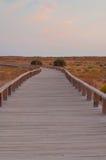 Pasarela de madera en las dunas, Algarve, Portugal, en la puesta del sol Foto de archivo libre de regalías