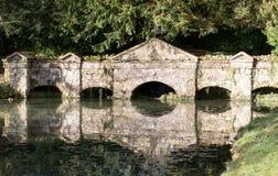 Pasarela de piedra vieja reflejada en el río Imagenes de archivo
