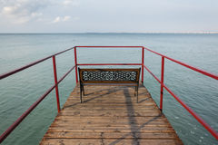 Pasarela vacía con un banco sobre el mar Foto de archivo