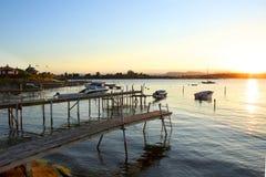 Pasarelas y barcos de motor de madera en el puerto deportivo en puesta del sol fotografía de archivo libre de regalías
