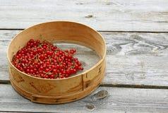 Pasas rojas en un tamiz en una tabla de madera Imagen de archivo