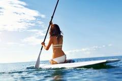 Pasatiempo La mujer coloca para arriba el batimiento, practicando surf recreacional fotos de archivo