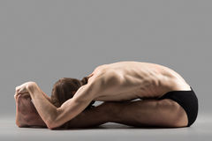 Paschimothanasana pose. Sporty muscular young yogi man doing sit-up, sitting in paschimottanasana pose, seated forward bend posture, studio shot on dark royalty free stock photography