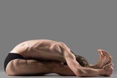 Paschimottanasana yoga posture. Sporty muscular young yogi man sitting in paschimottanasana (Intense Dorsal Stretch) pose, seated forward bend posture, exercise Stock Photos