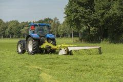 Pascolo che falcia con il trattore blu Fotografie Stock Libere da Diritti
