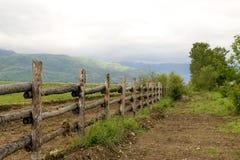 Pascolo e rete fissa verdi alle montagne Fotografia Stock