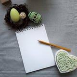 Pascua adornó los huevos en la jerarquía, libreta de papel en blanco en fondo gris foto de archivo libre de regalías