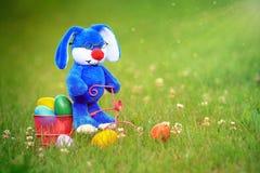 Pascua azul Bunny Riding un triciclo que lleva los huevos de Pascua Imagen de archivo