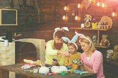 Pascua Bunny Costume Madre, padre y ni?o pintando los huevos de Pascua imagenes de archivo
