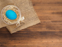Pascua coloreó el huevo en la arpillera y la tabla de madera vieja de la textura Imite para arriba para su tarjeta, cartel u otro Fotos de archivo libres de regalías