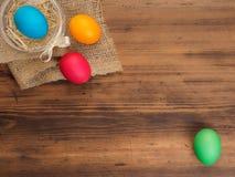 Pascua coloreó el huevo en la arpillera y la tabla de madera vieja de la textura Imite para arriba para su tarjeta, cartel u otro Fotografía de archivo libre de regalías