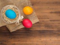 Pascua coloreó el huevo en la arpillera y la tabla de madera vieja de la textura Imite para arriba para su tarjeta, cartel u otro Fotografía de archivo