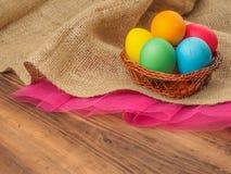 Pascua coloreó el huevo en una cestería con de la cesta Imite para arriba para su tarjeta, cartel u otro de felicitaciones diseño Fotografía de archivo libre de regalías