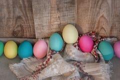 Pascua coloreó los huevos con el arco contra fondo texturizado de madera natural Fotos de archivo libres de regalías