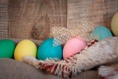 Pascua coloreó los huevos con el arco contra fondo texturizado de madera natural Imagen de archivo