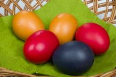 Pascua coloreó los huevos en la cesta Fotos de archivo