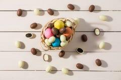 Pascua coloreó los huevos en una pequeña cesta considerada desde arriba Imagenes de archivo