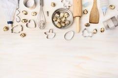 Pascua cuece las herramientas con los huevos de codornices y el cortador de la galleta en el fondo de madera blanco, visión super Fotos de archivo libres de regalías