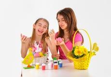 Pascua - dos muchachas, cesta con los huevos, pintura para colorear y un florero de flores Imagen de archivo