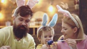 Pascua, familia, día de fiesta y concepto del niño - cierre para arriba de los huevos del colorante del niño pequeño, del padre y almacen de metraje de vídeo