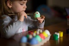 Pascua feliz El pintor de la niña pintó los huevos Niño que se prepara para Pascua Mano pintada Pintura del finger Concepto del a fotografía de archivo