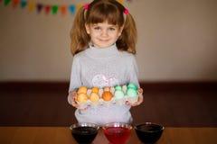 Pascua feliz El pintor de la ni?a pint? los huevos Ni?o que se prepara para Pascua Mano pintada Pintura del finger Concepto del a fotografía de archivo