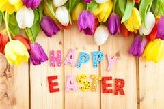 Pascua feliz escrita en letras multicoloras Foto de archivo libre de regalías
