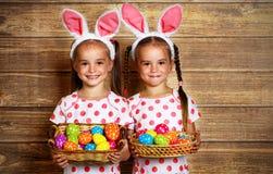 ¡Pascua feliz! hermanas lindas de las muchachas de los gemelos vestidas como conejos con e imagen de archivo