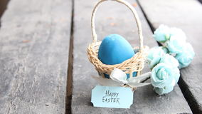 Pascua feliz Huevo azul en la tabla rústica y una cesta con una etiqueta