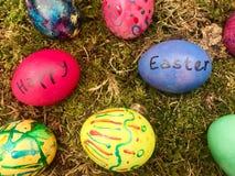 Pascua feliz - huevos de Pascua coloridos en musgo verde Imagen de archivo libre de regalías