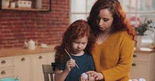 Pascua feliz La mamá enseña a sus huevos de pintura de la hija Familia feliz que se prepara para Pascua Oídos del conejito de la  almacen de metraje de vídeo