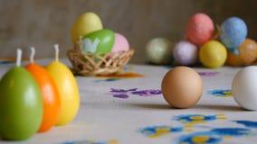 Pascua feliz la mano masculina da vuelta a un huevo blanco del pollo en la tabla huevos de Pascua olorful en el fondo