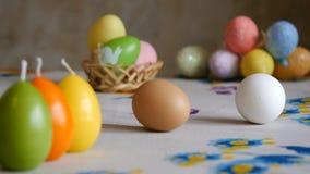 Pascua feliz las manos femeninas sacan los huevos de Pascua del cuadro dos velas coloridas y huevos de Pascua coloridos en