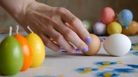 Pascua feliz Mano femenina que pone en los huevos de Pascua del cuadro dos velas coloridas y huevos de Pascua coloridos en