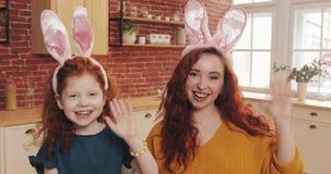 Pascua feliz Muchacha alegre del niño del pelirrojo con su oído del conejito de la mamá que lleva que hace la charla video con lo almacen de metraje de vídeo
