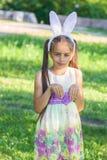 Pascua feliz: oídos del conejito de la niña que llevan adorable en un prado al aire libre imagen de archivo libre de regalías