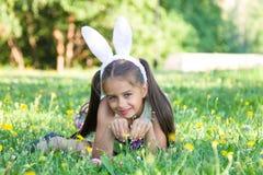 Pascua feliz: oídos del conejito de la niña que llevan adorable que mienten en el aire libre de la hierba imagenes de archivo