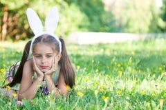 Pascua feliz: oídos del conejito de la niña que llevan adorable que mienten en un prado, inclinándose la cara en sus manos, al ai imágenes de archivo libres de regalías
