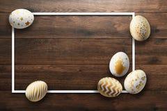 Pascua feliz, pintó los huevos de Pascua en un fondo de madera Modelo del oro blanco libre illustration