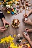 Pascua feliz Un grupo de personas que pinta los huevos de Pascua en la tabla de madera Familia feliz que se prepara para Pascua p Fotografía de archivo