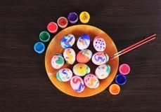 Pascua, huevos coloreados en una placa, los tarros de pintura y cepillo fotografía de archivo