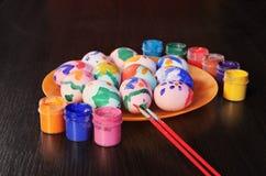 Pascua, huevos coloreados en una placa, los tarros de pintura y cepillo imágenes de archivo libres de regalías