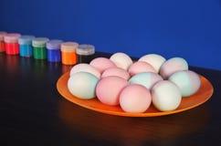 Pascua, huevos coloreados en una placa, tarros de pintura imagen de archivo