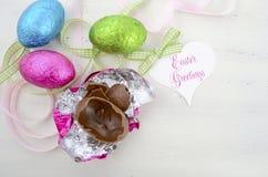 Pascua pica, se pone verde, y los huevos de chocolate en embalaje flexible azules Foto de archivo libre de regalías
