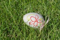 Pascua pintó los huevos con la cinta en hierba verde Imagenes de archivo
